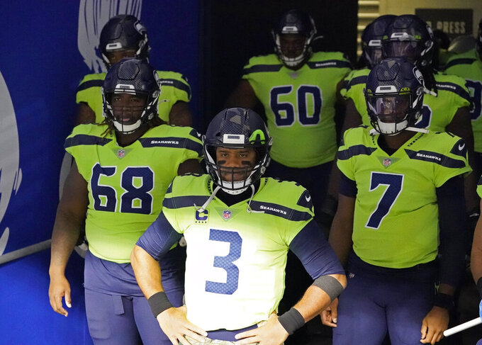 Seattle Seahawks quarterback Russell Wilson (3) stands in the tunnel with teammates, including offensive guard Damien Lewis (68) and backup quarterback Geno Smith (7) before an NFL football game against the Arizona Cardinals, Thursday, Nov. 19, 2020, in Seattle. (AP Photo/Elaine Thompson)