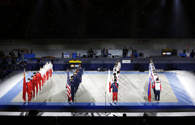Gymnasts from four countries China, from left, U.S., Japan and Russia line up for the opening ceremony of an international gymnastics meet in Tokyo on Sunday, Nov. 8, 2020.  The postponed Tokyo Olympics are to open in just under nine months. The International Olympic Committee and Japanese organizers have unwavering support from Japan's ruling party and Tokyo's municipal government. But there is a tiny murmur of resistance to the Olympic behemoth. A few voices in the national legislature question the wisdom of holding the Olympics in a pandemic. (AP Photo/Hiro Komae)