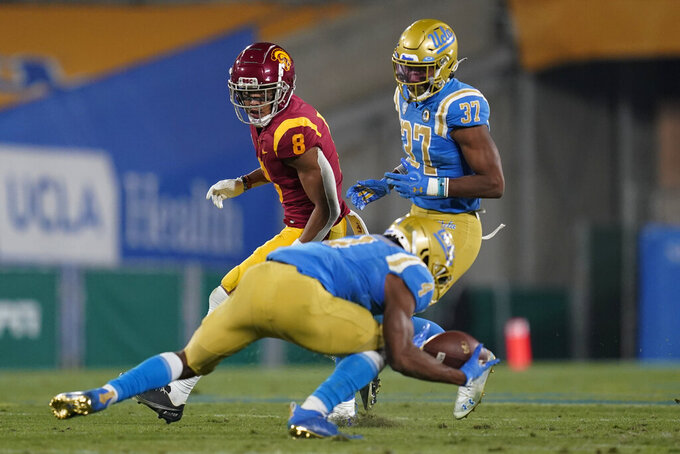 Southern California wide receiver Amon-Ra St. Brown, left, watches as UCLA defensive back Stephan Blaylock (4) intercepts a pass during the third quarter of an NCAA college football game Saturday, Dec 12, 2020, in Pasadena, Calif. UCLA defensive back Quentin Lake is at right. (AP Photo/Ashley Landis)