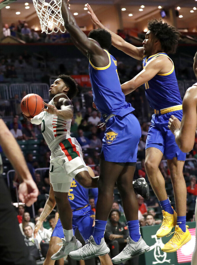 Miami guard Chris Lykes, left, goes to the basket as Pittsburgh forward Eric Hamilton, center, and guard Justin Champagnie, right, defend during the second half of an NCAA college basketball game, Sunday, Jan. 12, 2020, in Coral Gables, Fla. Miami won 66-58. (AP Photo/Lynne Sladky)