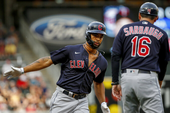 Cleveland Indians' Bobby Bradley, left, celebrates with third base coach Mike Sarbaugh, right, after hitting a two run home run against the Minnesota Twins in the first inning of a baseball game Friday, June 25, 2021, in Minneapolis. (AP Photo/Bruce Kluckhohn)