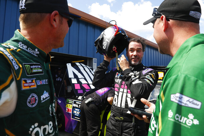Jimmie Johnson, center, talks with Clint Bowyer, left, during practice for a NASCAR Cup Series auto race at Michigan International Speedway in Brooklyn, Mich., Saturday, Aug. 10, 2019. (AP Photo/Paul Sancya)