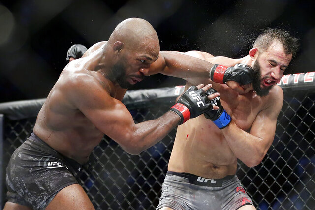 Jon Jones, left, connects a punch on Dominick Reyes, right, during a light heavyweight mixed martial arts bout at UFC 247 Sunday, Feb. 9, 2020, in Houston. (AP Photo/Michael Wyke)