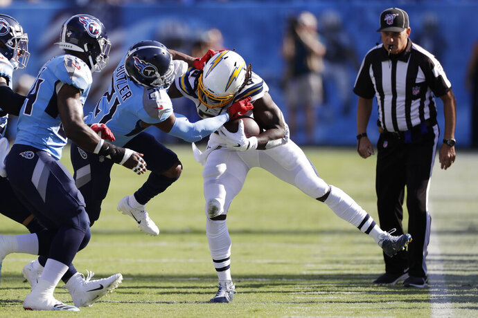 Los Angeles Chargers running back Melvin Gordon, center, is pushed out of bounds by Tennessee Titans cornerback Malcolm Butler (21) in the first half of an NFL football game Sunday, Oct. 20, 2019, in Nashville, Tenn. (AP Photo/James Kenney)