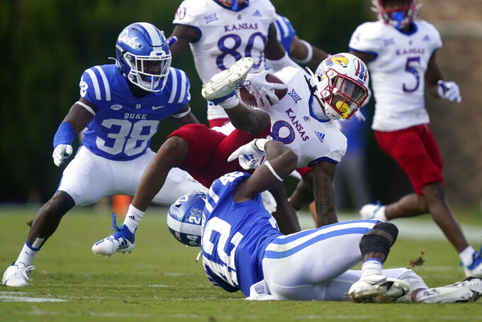 Kansas wide receiver Kwamie Lassiter II (8) is tackled by Duke linebacker Shaka Heyward (42) during the first half of an NCAA college football game in Durham, N.C., Saturday, Sept. 25, 2021. (AP Photo/Gerry Broome)