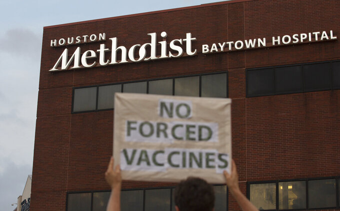 FILE - In this June 7, 2021, file photo, a person holds a sign to protest at Houston Methodist Hospital in Baytown, Texas, a policy that says hospital employees must get vaccinated against COVID-19 or lose their jobs. A  federal judge dismissed their lawsuit, saying if workers don't like the rule, they can go find another job. (Yi-Chin Lee/Houston Chronicle via AP, File)