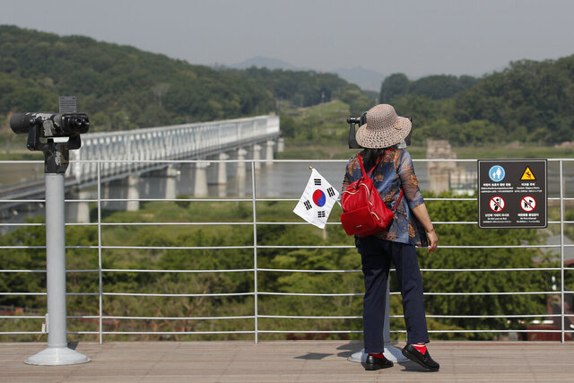 A visitor carrying a South Korean flag uses binoculars to view the northern side at the Imjingak Pavilion in Paju, South Korea, Tuesday, June 9, 2020. North Korea said Tuesday it will cut off all communication channels with South Korea as it escalates its pressure on the South for failing to stop activists from floating anti-Pyongyang leaflets across their tense border. (AP Photo/Lee Jin-man)