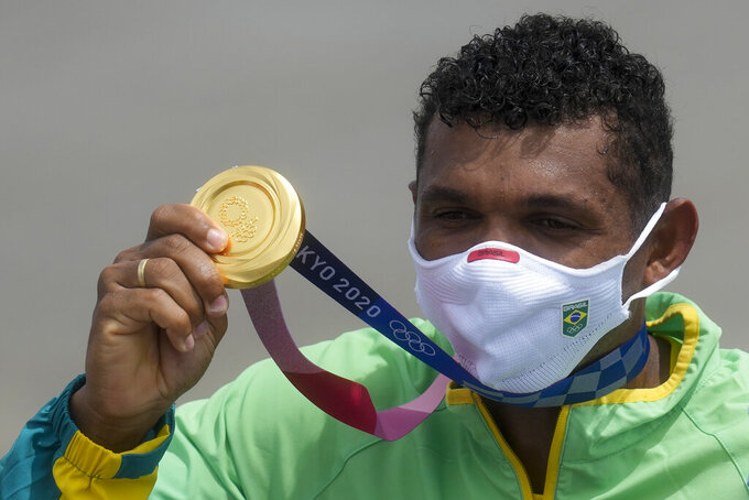 Isaquias Queiroz dos Santos, of Team Brazil, holds up his gold medal during the medal ceremony for men's canoe single 1000m final at the 2020 Summer Olympics, Saturday, Aug. 7, 2021, in Tokyo, Japan.(AP Photo/Lee Jin-man)