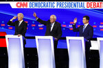 From left, Democratic presidential candidate former Vice President Joe Biden, Sen. Bernie Sanders, I-Vt.,and former South Bend Mayor Pete Buttigieg look to answer a question Tuesday, Jan. 14, 2020, during a Democratic presidential primary debate hosted by CNN and the Des Moines Register in Des Moines, Iowa. (AP Photo/Patrick Semansky)