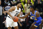 Colorado forward Evan Battey, left, looks to pass the ball as UCLA forward Jalen Hill defends in the first half of an NCAA college basketball game Saturday, Feb. 22, 2020, in Boulder, Colo. (AP Photo/David Zalubowski)