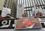 South Korean small and medium-sized business owners with a defaced image of Japanese Prime Minister Shinzo Abe shout slogans during a rally calling for boycott of Japanese products in front of the Japanese embassy in Seoul, South Korea, Monday, July 15, 2019. South Korea and Japan last Friday, July 12, failed to immediately resolve their dispute over Japanese export restrictions that could hurt South Korean technology companies, as Seoul called for an investigation by the United Nations or another international body. The signs read: