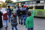 Syrian refugees who will stay in Lebanon wave goodbye to their relatives in a bus that will take them home to Syria, in Beirut, Lebanon, Tuesday, Dec. 3, 2019. Hundreds of Syrian refugees have returned home in the first batch to leave Lebanon since protests broke out in the country more a month ago. Lebanon is hosting about 950,000 registered Syrian refugees according to the U.N. refugee agency. The government estimates the true number of Syrian refugees in the country at 1.5 million. (AP Photo/Hussein Malla)