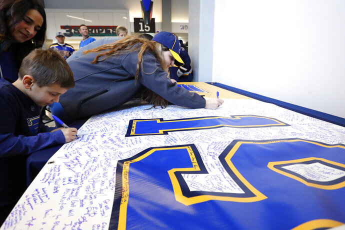 Fans sign a banner sending well wishes to St. Louis Blues' Jay Bouwmeester prior to the start of an NHL hockey game against the Nashville Predators Saturday, Feb. 15, 2020, in St. Louis. Bouwmeester suffered a cardiac episode while on the bench during a game Tuesday, Feb. 11, 2020, in Anaheim, Calif. (AP Photo/Billy Hurst)