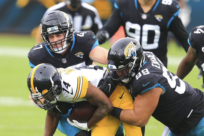 Jacksonville Jaguars linebacker Joe Schobert, left, and defensive tackle Daniel Ekuale (99) stop Pittsburgh Steelers wide receiver Ray-Ray McCloud (14) after a reception during the first half of an NFL football game, Sunday, Nov. 22, 2020, in Jacksonville, Fla. (AP Photo/Matt Stamey)