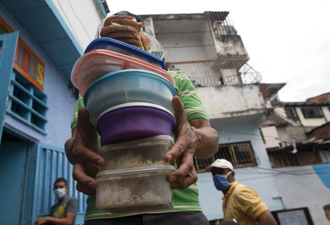 A volunteer carries containers with rice, chicken and salad to be given to residents at the San Antonio de Padua soup kitchen in the Petare neighborhood of Caracas, Venezuela, Thursday, June 10, 2021, amid the new coronavirus pandemic. (AP Photo/Ariana Cubillos)
