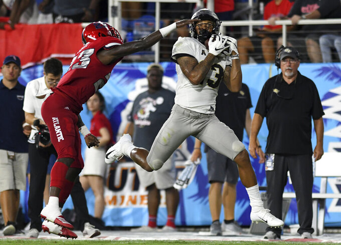 UCF wide receiver Gabriel Davis hauls in a pass for a big gain as Florida Atlantic cornerback James Pierre (23) defends during the first half of an NCAA college football game Saturday, Sept. 7, 2019, in Boca Raton, Fla. (AP Photo/Jim Rassol)