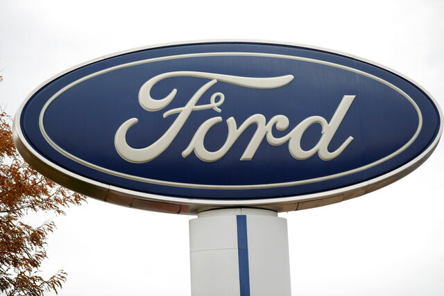 FILE - In this Oct. 20, 2019, file photo, the company logo stands over a long row of unsold vehicles at a Ford dealership in Littleton, Colo. Ford is recalling over 240,000 SUVs and cars worldwide because a suspension part can fracture and increase the risk of a crash. (AP Photo/David Zalubowski, File)