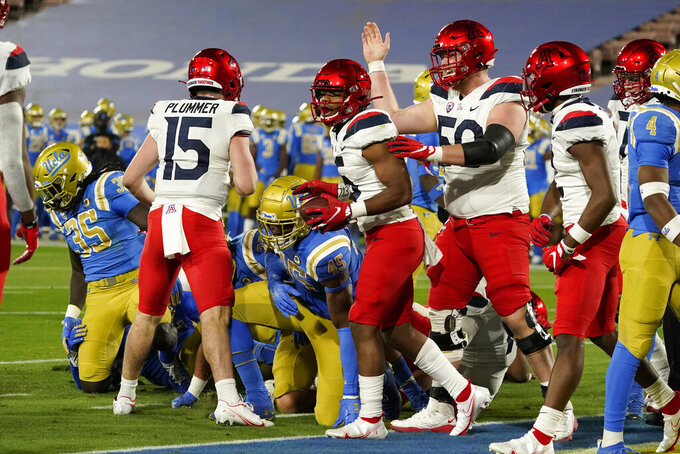 Arizona running back Michael Wiley, center with ball, celebrates his rushing touchdown against UCLA during the first half of an NCAA college football game Saturday, Nov. 28, 2020, in Pasadena, Calif. (AP Photo/Marcio Jose Sanchez)