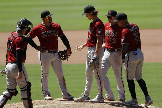Arizona Diamondbacks starting pitcher Luke Weaver, middle, meets players on the mound before leaving during the fourth inning of the team's baseball game against the San Diego Padres, Monday, July 27, 2020, in San Diego. (AP Photo/Gregory Bull)
