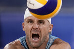 Jacob Gibb (1), of the United States, returns a shot against Germany during a men's beach volleyball match at the 2020 Summer Olympics, Monday, Aug. 2, 2021, in Tokyo, Japan. (AP Photo/Felipe Dana)