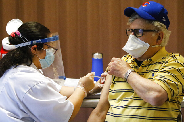 Walgreens pharmacist Stephanie Rosado, left, administers a Moderna COVID-19 vaccine shot to Peter Murdakes, a housing board member at the AHEPA apartments in Merrillville, on Monday./The Times via AP)