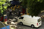 Police officers inspect a vehicle entering the WestLite Toh Guan dormitory, which has been declared an isolation area under the Infectious Diseases Act, following a spike in the number of COVID-19 cases in several foreign worker dormitories in Singapore, Friday, April 10, 2020. The tiny city-state of Singapore, with under six million people, has been hailed as a model in its swift response to the virus in the early days. But it overlooked the massive pool of migrant workers living in close quarters where social distancing is impossible and conditions are ripe for the virus spread. (AP Photo)