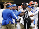 Florida head coach Dan Mullen, center, is restrained during a verbal confrontation with Vanderbilt coaches and players in the first half of an NCAA college football game Saturday, Oct. 13, 2018, in Nashville, Tenn. (AP Photo/Mark Humphrey)