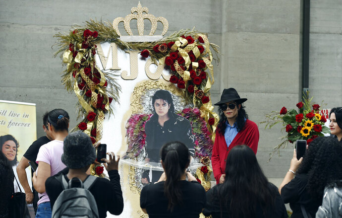 Michael Jackson impersonator Rem Garza of Long Beach, Calif., poses next to a shrine to the late pop star outside his final resting place in Holly Terrace at Forest Lawn Cemetery, Tuesday, June 25, 2019, in Glendale, Calif. Tuesday marks the 10th anniversary of Jackson's death. (Photo by Chris Pizzello/Invision/AP)