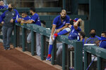 Texas Rangers' Rougned Odor sits on the rail by other teammates in the dugout during an intrasquad practice baseball game at Globe Life Field in Arlington, Texas, Monday, July 6, 2020. (AP Photo/Tony Gutierrez)