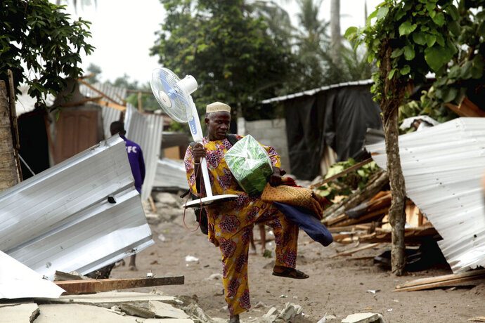 A man carries his belongings salvaged from the shack he lived in near the airport in Abidjan, Ivory Coast, Thursday Jan. 23, 2020. Construction crews leveled shacks near the airport, part of a crackdown on informal settlements following the death of a teenage boy who had managed to hide aboard as a stowaway on a flight to Paris earlier in the month. (AP Photo/Diomande Ble Blonde)