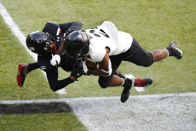 Cincinnati defensive back Coby Bryant, left, knocks Army running back Tyrell Robinson out of bounds during the second half of an NCAA college football game Saturday, Sept. 26, 2020, in Cincinnati, Ohio. Cincinnati beat Army 24-10. (AP Photo/Jay LaPrete)