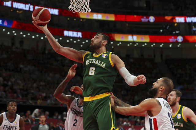 "FILE - In this Sept. 15, 2019, file photo, Andrew Bogut of Australia puts up a shot over Amath M'Baye, left, and Evan Fournier of France during their third placing match for the FIBA Basketball World Cup at the Cadillac Arena in Beijing. NBA veteran Bogut says players were ""used like pawns"