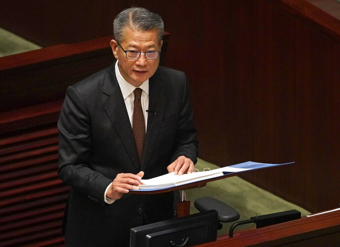 Hong Kong's Financial Secretary Paul Chan delivers his annual budget speech at the Legislative Council in Hong Kong Wednesday, Feb. 26, 2020.  Hong Kong's government is proposing a nearly $1,300 cash handout for each resident over 18 years old to help alleviate hardships brought on by the spreading viral outbreak and prolonged political protests.(AP Photo/Vincent Yu)