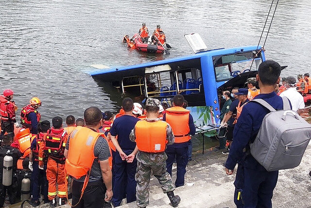 In this photo released by Xinhua News Agency, rescuers watch as a bus that fell into a lake is recovered in the Xixiu District of Anshun, southwestern China's Guizhou Province, Tuesday, July 7, 2020. Authorities say dozens were killed Tuesday when a bus ran through a roadside fence and plunged into a lake in the southwestern Chinese city. (Long Rui/Xinhua via AP)
