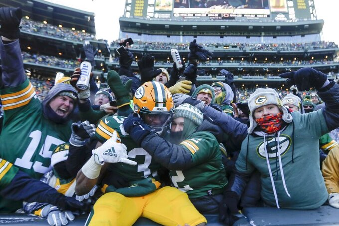 Green Bay Packers' Aaron Jones celebrates with fans after running for a touchdown during the second half of an NFL football game against the Chicago Bears Sunday, Dec. 15, 2019, in Green Bay, Wis. (AP Photo/Morry Gash)