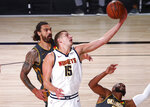 Denver Nuggets center Nikola Jokic (15) shoots the ball against the Oklahoma City Thunder during the first half of an NBA basketball game Monday, Aug. 3, 2020, in Lake Buena Vista, Fla. (Kim Klement/Pool Photo via AP)