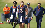 Denver Broncos quarterback Drew Lock, front, heads off the practice field with, from back left, quarterback Teddy Bridgewater (5), quarterbacks coach Mike Shula and offensive quality control coach Chris Cook after an NFL football training camp practice at the team's headquarters Tuesday, Aug. 10, 2021, in Englewood, Colo. (AP Photo/David Zalubowski)