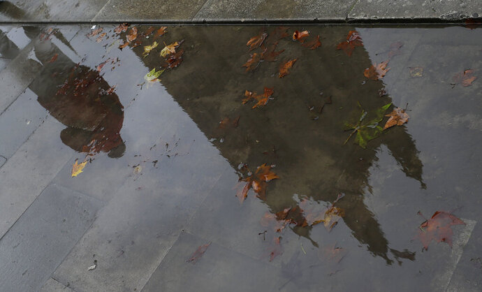 Britain's Parliament buildings are reflected in a muddy puddle in London, Monday, Oct. 21, 2019. The European Commission says the fact that British Prime Minister Boris Johnson did not sign a letter requesting a three-month extension of the Brexit deadline has no impact on whether it is valid and that the European Union is considering the request. (AP Photo/Kirsty Wigglesworth)