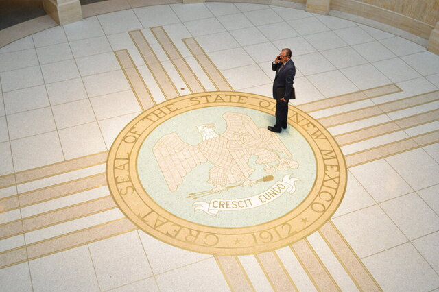 An aide speaks on the phone at the New Mexico Roundhouse while state lawmakers debate a state budget and early childhood education on Wednesday, Feb. 5, 2020, in Santa Fe, N.M. (AP Photo/ Russell Contreras)
