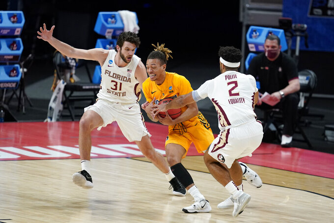 UNC-Greensboro's Kaleb Hunter (44) goes to the basket against Florida State's Wyatt Wilkes (31) and Anthony Polite (2) during the first half of a first-round game in the NCAA men's college basketball tournament at Banker's Life Fieldhouse, Saturday, March 20, 2021, in Indianapolis. (AP Photo/Darron Cummings)