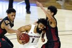 Arizona State guard Remy Martin (1) tries to drive past San Diego State forward Matt Mitchell, left, and guard Trey Pulliam, right, during the first half of a college basketball game Thursday, Dec. 10, 2020, in Tempe, Ariz. (AP Photo/Ross D. Franklin)