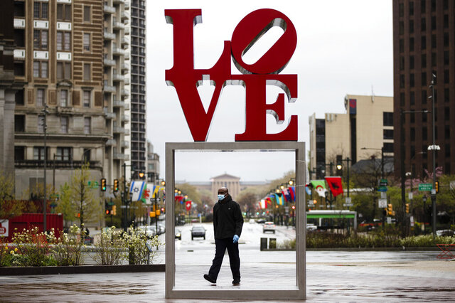 A person wearing a protective face mask and gloves as a precaution against the coronavirus walks by the Robert Indiana sculpture