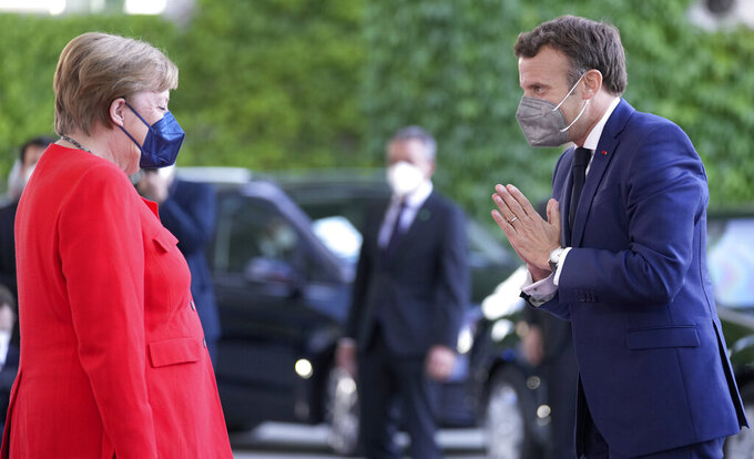 German Chancellor Angela Merkel, left, welcomes the President of France, Emmanuel Macron, right, for a meeting at the chancellery in Berlin, Germany, Friday, June 18, 2021. (AP Photo/Michael Sohn)