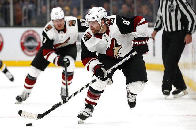 FILE - In this Feb. 8, 2020, file photo, Arizona Coyotes' Phil Kessel (81) moves the puck during the second period of an NHL hockey game against the Boston Bruins, in Boston. Injuries led to a disappointing first season in Arizona for Phil Kessel. Now that he's had time to heal up during the NHL's pause to the season, the high-scoring forward could help the Coyotes make a deep run once the season resumes. (AP Photo/Winslow Townson, File)
