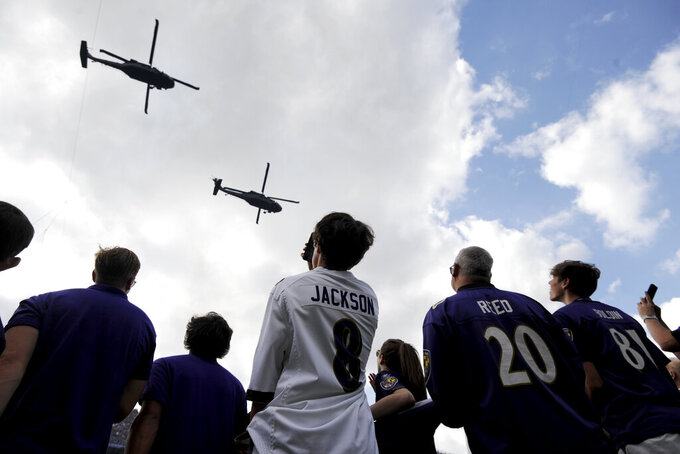 Fans watch as two helicopters conduct a flyover prior to an NFL football game between the Baltimore Ravens and the Cleveland Browns Sunday, Sept. 29, 2019, in Baltimore. (AP Photo/Gail Burton)