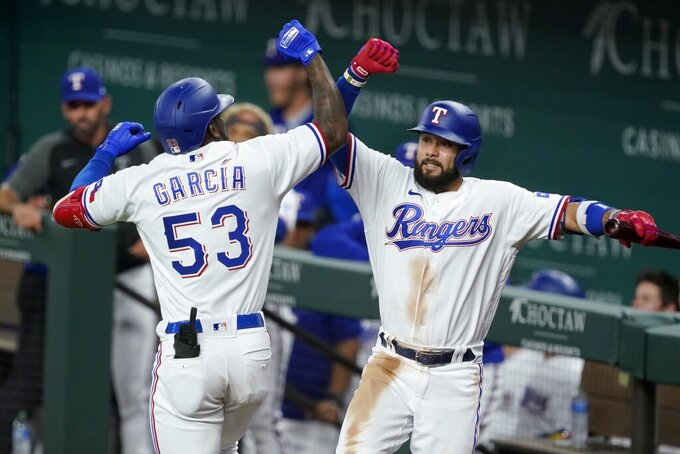 Texas Rangers' Adolis Garcia (53) and Isiah Kiner-Falefa, right, celebrate after Garcia hit a solo home run in the second inning of a baseball game against the New York Yankees in Arlington, Texas, Monday, May 17, 2021. (AP Photo/Tony Gutierrez)