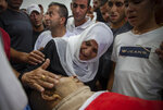 A Palestinian woman mourns while taking a farewell look at the body of Raed Jadallah, 39, who was killed by Israeli forces at the western entrance of his village while returning from work in the early hours of Wednesday morning, during his funeral, in the West Bank village of Beit Ur al-Tahta, Wednesday, Sep. 1, 2021. (AP Photo/Majdi Mohammed)