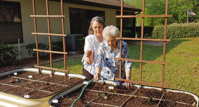 In this April 12, 2020 photo, Brenda Flowers, left, and 96-year-old Lorraine Tyree, water their plants in Crystal River, Fla. Backyard gardeners are coming together, mostly virtually, to learn and share stories on how to grow vegetables, fruits and flowers as the novel coronavirus raises fears about disruptions in food supplies and the cost of food in a down economy. (Ed Flowers via AP)