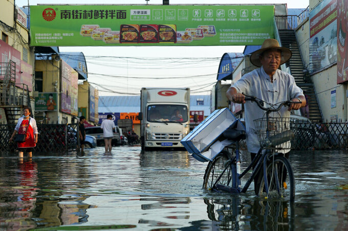 FILE - In this Monday, July 26, 2021 file photo, a man carries goods on his bicycle as he walks out of the the Yubei Agricultural and Aquatic Products World in Xinxiang in central China's Henan Province. Scientists say there's something different this year from the recent drumbeat of climate weirdness. This summer a lot of the places hit by weather disasters are not used to getting extremes and many of them are wealthier, which is different from the normal climate change victims. That includes unprecedented deadly flooding in Germany and Belgium, 116-degree heat records in Portland, Oregon and similar blistering temperatures in Canada, along with wildfires. Now Southern Europe is seeing scorching temperatures and out-of-control blazes too. And the summer of extremes is only getting started. Peak Atlantic hurricane and wildfire seasons in the United States are knocking at the door. (AP Photo/Dake Kang, File)