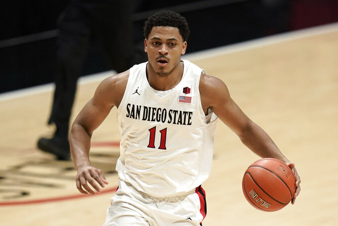 San Diego State forward Matt Mitchell (11) controls the ball during the first half of an NCAA college basketball game against Boise State Saturday, Feb 27, 2021, in San Diego. (AP Photo/Gregory Bull)